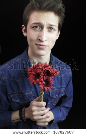 Handsome young man holding a bouquet of red flowers - stock photo