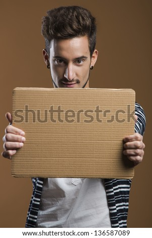 Handsome young man holding a card board - stock photo