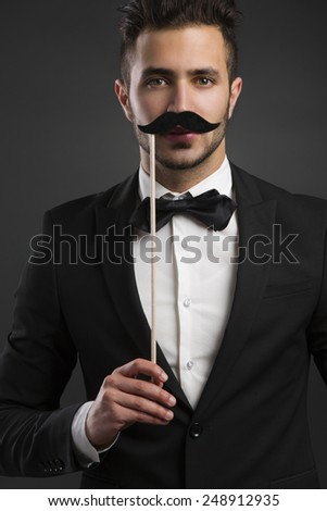 Handsome young man holding a fake mustache - stock photo