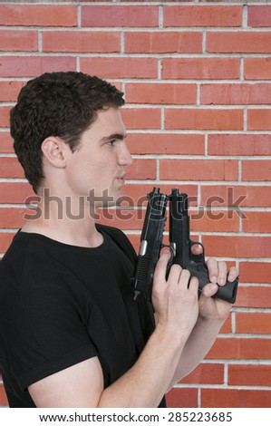 Handsome young man holding a hand gun pistol - stock photo