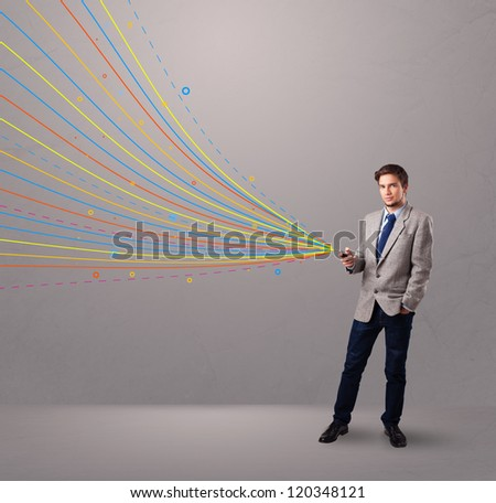 handsome young man holding a phone with colorful abstract lines - stock photo