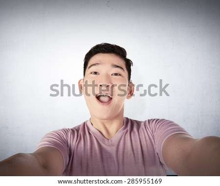 Handsome young man holding camera and making selfie isolated over grunge wall background - stock photo