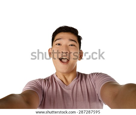 Handsome young man holding camera and making selfie isolated over white background - stock photo
