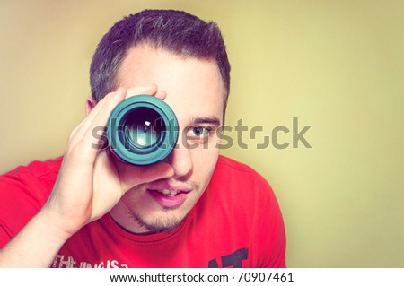 Handsome young man holding camera lens like it was spyglass - stock photo