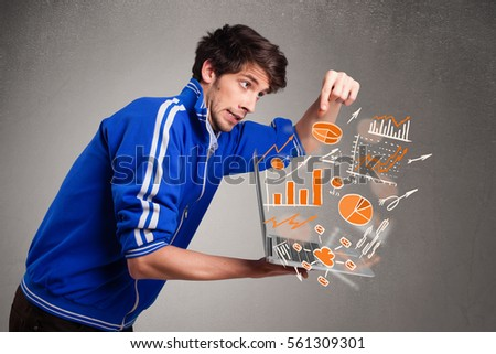 Handsome young man holding laptop with graphs and statistics