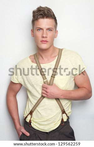 Handsome young man holding suspenders against white background - stock photo