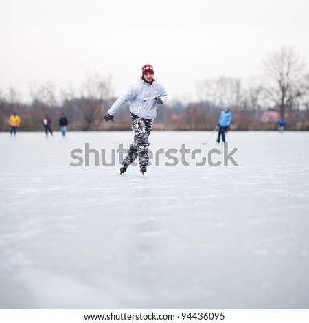 Handsome young man ice skating outdoors on a pond on a cloudy winter day (color toned image; shallow DOF) - stock photo