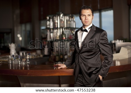 Handsome young man in a black tuxedo at a round bar holding whiskey in his hand; shallow depth of field, focus on face. - stock photo