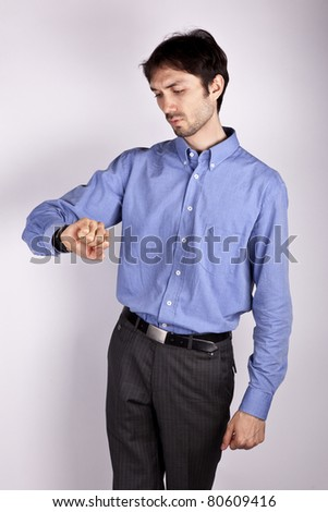 handsome young man in a blue shirt stands and looks at his watch and thinks something - stock photo