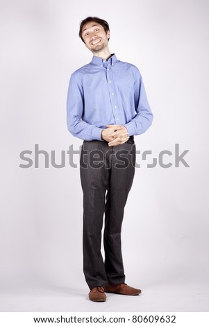 handsome young man in a blue shirt stands with folded hands and bowed his head and artfully something conceived and grins - stock photo