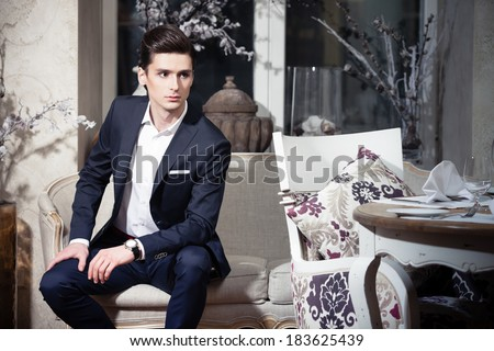 Handsome young man in a classic suit sitting on a sofa in restaurant - stock photo