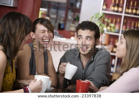 Handsome young man in a coffee house surrounded by pretty women - stock photo