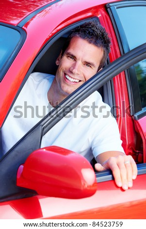 Handsome young man in a red car. - stock photo