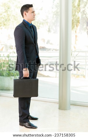 Handsome young man in a suit and carrying a briefcase waiting to be interviewed for a job - stock photo