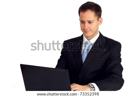 Handsome young man in a suit by his laptop