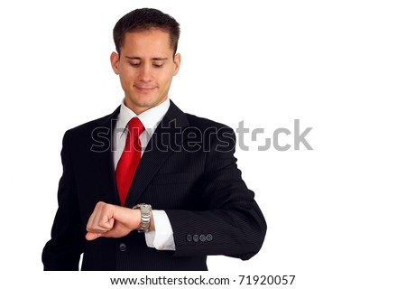 Handsome young man in a suit checking the time on his wrist watch - stock photo