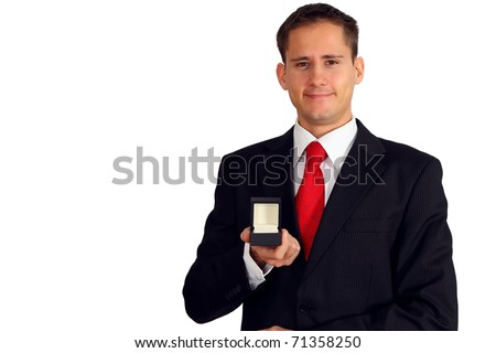 Handsome young man in a suit presenting something in a small box