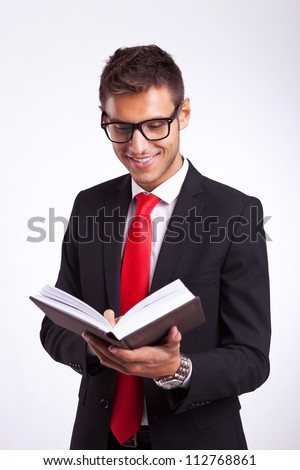 Handsome young man in a suit reading an interesting book and smiling - stock photo