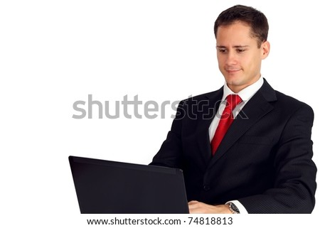 Handsome young man in a suit working on his laptop - stock photo