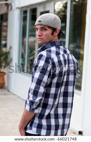 Handsome young man in an urban lifestyle fashion pose in a downtown scene wearing a baseball cap.