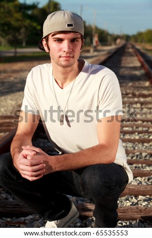 Handsome young man in an urban lifestyle fashion pose kneeling on a railroad track. - stock photo
