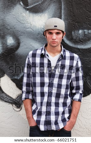 Handsome young man in an urban lifestyle fashion pose leaning against a graffiti wall wearing a baseball cap. - stock photo
