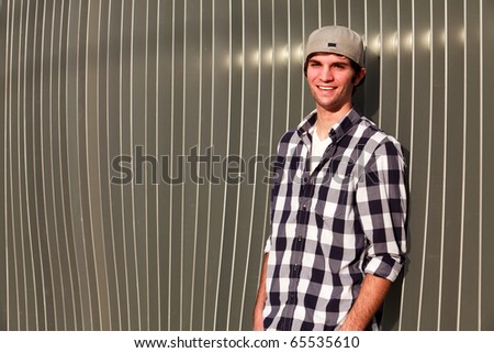 Handsome young man in an urban lifestyle fashion pose leaning against a modern fence wall wearing a baseball cap. - stock photo