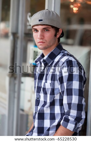 Handsome young man in an urban lifestyle fashion pose leaning against a store front wearing a baseball hat. - stock photo