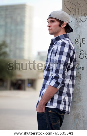 Handsome young man in an urban lifestyle fashion pose leaning against a utility pole wearing a baseball cap. - stock photo