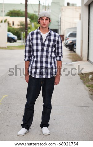 Handsome young man in an urban lifestyle fashion pose standing in a downtown alley wearing a baseball cap. - stock photo