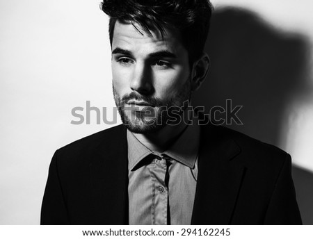 handsome young man in business suit on grey background