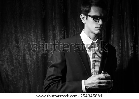 Handsome young man in business suit stay on drapes background. Black and white portrait. - stock photo