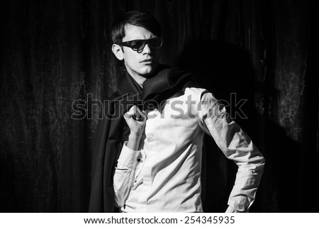 Handsome young man in business suit stay on drapes background. Holding jacket. Black and white portrait. - stock photo