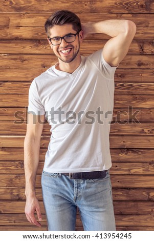 Handsome young man in casual clothes and eyeglasses is looking at camera and smiling, standing against wooden wall - stock photo