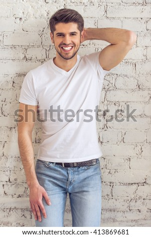 Handsome young man in casual clothes is looking at camera and smiling, standing against white brick wall - stock photo