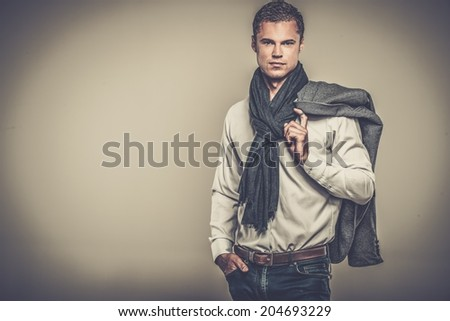 Handsome young man in casual jacket and neck scarf - stock photo