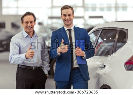 Handsome young man in classic blue suit and middle aged man are smiling, looking at camera and showing Ok sign while standing in a motor show