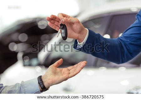 Handsome young man in classic blue suit is giving car keys to middle aged customer in a motor show - stock photo