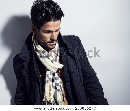handsome young man in coat and scarf with fit body posing on grey background - stock photo