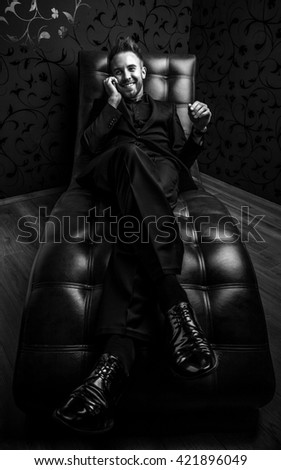 Handsome young man in dark suit relaxing on luxury sofa. Black-white photo. - stock photo