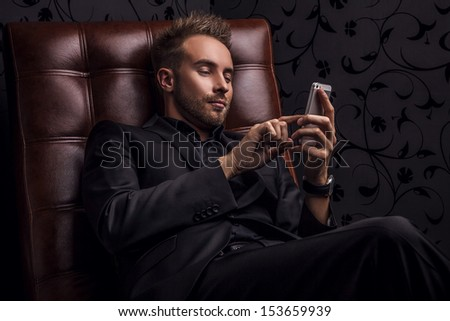 Handsome young man in dark suit relaxing on luxury sofa with mobile phone.