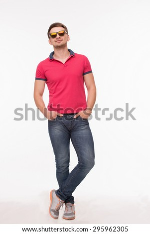 Handsome young man in full lenght. Sporty man in sunglasses posing withhis arms in pockrts isolated on white background. - stock photo