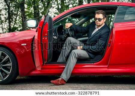Handsome young man in his new sports car.  - stock photo