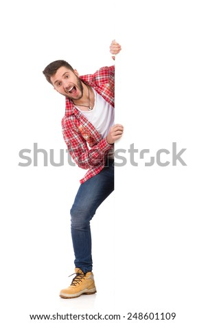 Handsome young man in jeans and lumberjack shirt standing behind white banner and shouting. Full length studio shot isolated on white. - stock photo