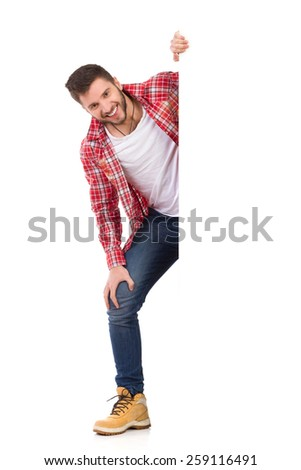Handsome young man in jeans and lumberjack shirt standing behind white banner and smiling. Full length studio shot isolated on white. - stock photo