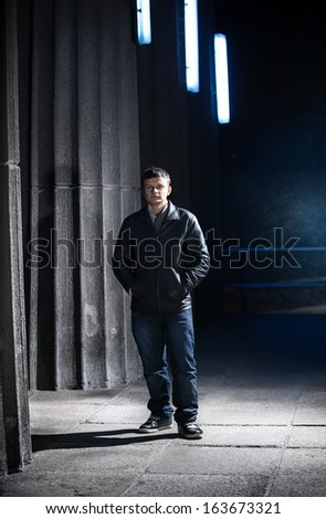 Handsome young man in leather coat posing at night against big columns - stock photo