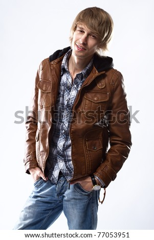 Handsome young man in leather jacket, studio portrait - stock photo