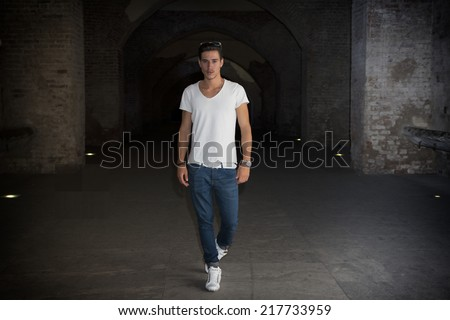 Handsome young man in old building walking inside gallery, looking at camera, full figure shot - stock photo