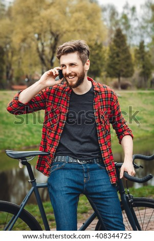 Handsome Young Man In Red Shirt And Blue Jeans Stops Cycling, To Speak On His Phone In An Alley With Green Trees Near Lake - stock photo
