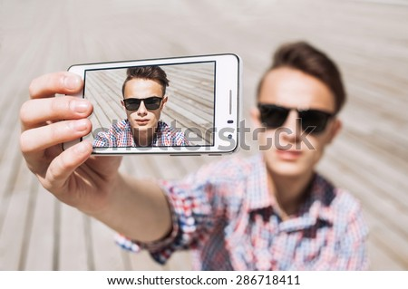 Handsome young man in shirt holding camera and making selfie - stock photo